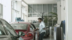 Happy swarthy guy dancing near the car and show a thumb up in car dealership. Happy swarthy guy looks in camera and shows a thumbs up. Handsome man start dancing stock video footage