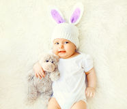 Happy sweet baby in knitted hat with a rabbit ears and teddy bear toy. Lying on bed, top view Royalty Free Stock Photo