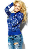 Happy sweet cute smiling blonde woman in blue sweater. Portrait of beautiful happy sweet smiling blonde woman girl in casual hipster warm winter clothes, in blue Royalty Free Stock Photo