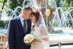 Happy sweet newly wedding couple near fountain Stock Images
