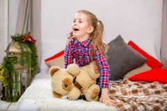 Happy sweet young girl in a checkered blue-red dress sitting on a bed with a teddy bear and laughing stock images