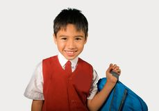 Happy and sweet young schoolboy 7 or 8 years old in school uniform smiling cheerful and excited ready to go back to school carryin. Isolated portrait of happy royalty free stock image