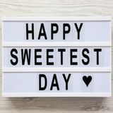 `Happy Sweetest Day` word on modern board over white wooden background, top view. From above, flat lay, overhead. `Happy Sweetest Day` word on modern board over stock photo
