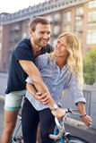 Happy Sweethearts Riding Bicycle at the Street Royalty Free Stock Images