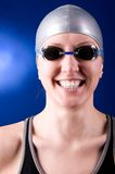 Happy swimmer. Portrait of a laughing looking at camera woman swimmer on blue background Stock Photo