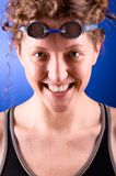 Happy swimmer. Portrait of a laughing looking at camera woman swimmer on blue background Royalty Free Stock Photos