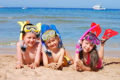 Happy swimmers; snorkelers. Three kids laying on the beach wearing snorkeling equipment Stock Images