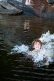 Happy swimming boy. Young boy playing in a lake in Haliburton County Ontario royalty free stock images