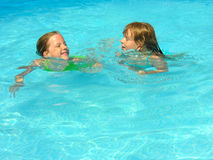 Happy swimming friends. TWo yound girls swimming and laughing in the swimming pool Royalty Free Stock Photos