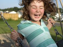 Happy swinger. Young girl enjoying playing on a swing at a local playground Royalty Free Stock Image