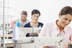 Happy Tailor With Colleagues Working In Factory Royalty Free Stock Images