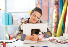 Happy tailor woman hugging sewing machine Royalty Free Stock Image