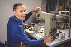 Happy tailor working on the machine Royalty Free Stock Photo