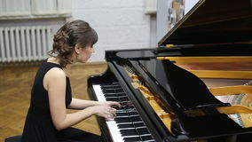 Happy talented young lady playing grand piano stock footage
