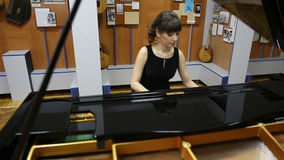 Happy talented young lady playing grand piano stock video footage