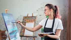 Happy talented young woman painter enjoying drawing picture at art studio medium shot. Smiling hipster creative female artist having good time during working stock footage