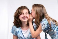 Happy Talk. 2 young girls telling secrets Stock Photo