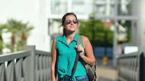 Happy tanned backpacker female in sunglasses walking at summer park area enjoying vacation