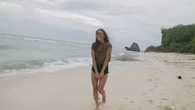 Happy tanned girl with long hair walking along the sandy beach stock footage