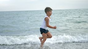 Happy tanned little boy running on beach enjoying childhood during summer vacation slow motion