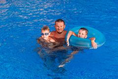 4848e547e4 Happy tanned man with two kids swimming in blue outdoor pool stock photos