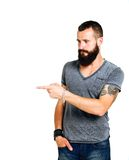 Happy Tattooed bearded man presenting and showing Stock Photography