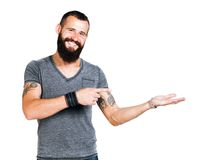 Happy Tattooed bearded man presenting and showing. With copy space for your text isolated on white background stock image