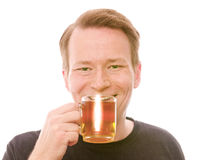 Happy tea. Young smiling man drinking some tea - isolated on white and retouched Stock Image