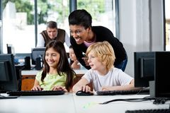 Happy Teacher Assisting Schoolchildren In Using. Happy female teacher assisting schoolchildren in using computer at school Royalty Free Stock Images