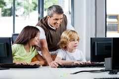 Happy Teacher Assisting Schoolchildren In Using. Happy male teacher assisting schoolchildren in using desktop PC at computer lab Royalty Free Stock Image