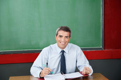 Happy Teacher With Binder And Pen Sitting At Desk. Portrait of happy male teacher with binder and pen sitting at desk in classroom Royalty Free Stock Photos