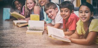 Happy teacher with children lying down while reading books stock photos
