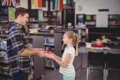 Happy teacher giving book to schoolgirl in library. Happy teacher giving book to girl in library at school Stock Photography