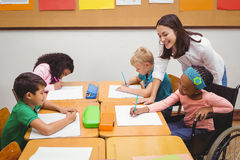 Happy teacher helping her students Royalty Free Stock Images