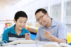 Happy teacher helping his student to count. Portrait of happy male teacher helping his student to count while sitting in the library royalty free stock images