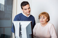 Happy Teacher Helping Senior Student In Computer Class Royalty Free Stock Images