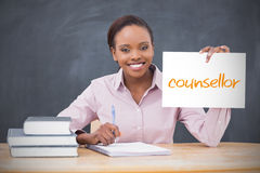 Happy teacher holding page showing counsellor. In her classroom at school royalty free stock photo