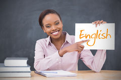 Happy teacher holding page showing english. In her classroom at school royalty free stock image