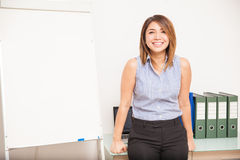 Happy teacher leaning on her desk Royalty Free Stock Image