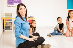 Happy teacher in a preschool classroom. Portrait of a Latin teacher enjoying her job with her preschool students and smiling royalty free stock photography