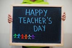 Happy teacher`s day. Boy hold chalkboard with blue inscription