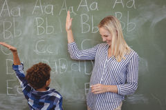 Happy teacher and schoolboy giving high five in classroom. At school stock photo
