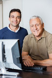 Happy Teacher And Senior Man At Computer Desk In Classroom Royalty Free Stock Image