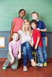 Happy teacher and students. In elementary school in front of a chalkboard Royalty Free Stock Photo