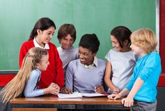 Happy Teacher Teaching Schoolchildren At Desk In Stock Photography