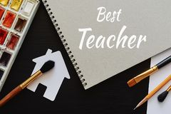 Happy Teachers' Day greeting card. Text Best Teacher and school painting supplies stock images