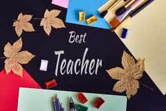 Happy Teachers' Day greeting card. Text Best Teacher and school supplies on black wooden background stock photography