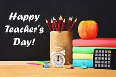 Happy Teachers Day. School and office supplies on a black chalkboard background. Back to school.