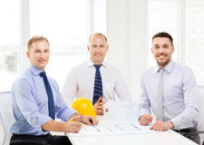 Happy team of architects and designers in office. Business, architecture and office concept - happy team of architects and designers in office Royalty Free Stock Photos