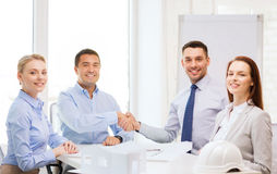 Happy team of architects and designers in office. Business, architecture and office concept - happy team of architects and designers in office shaking hands Stock Photo